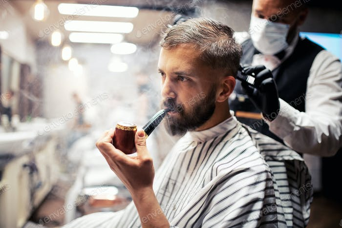Hipster man client visiting haidresser and hairstylist in barber shop, smoking a pipe.