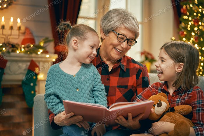 Grandmother reading  to granddaughters near Christmas tree.