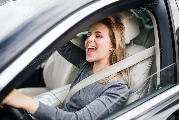Cheerful young woman driver sitting in car, driving.