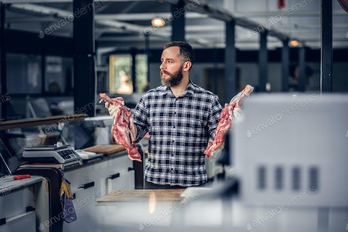 Portrait of a bearded meat man holds fresh cut meat.