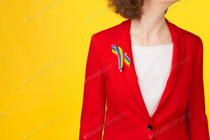 concepto homosexual y lgtb - cerca de la mujer que lleva cinta de conciencia del orgullo gay en su pecho