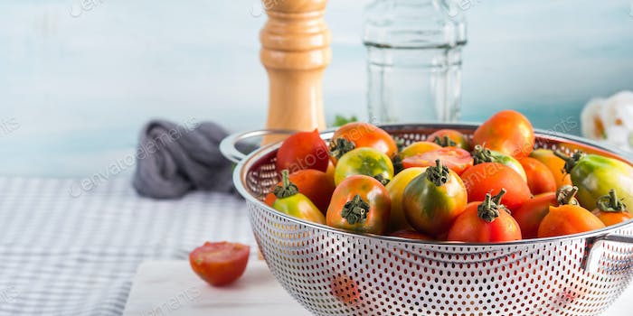 Italian tomatoes in a colander on table