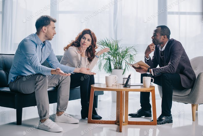 Quarreling couple talking to african american psychiatrist in office