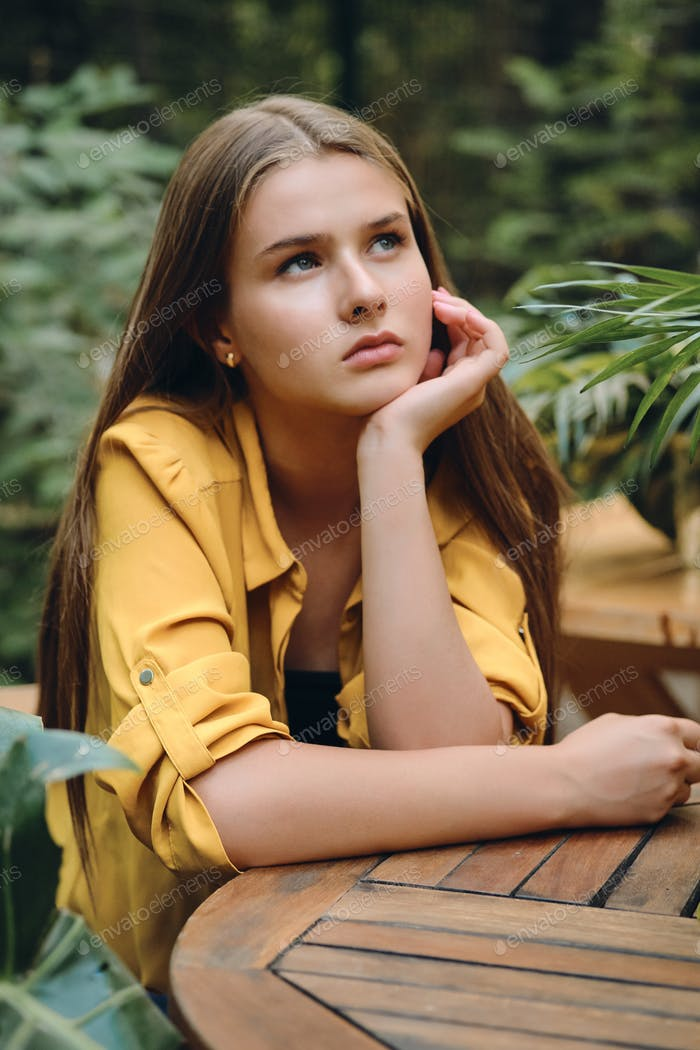 Pensive brown haired girl in yellow shirt thoughtfully looking up among green leaves in city park