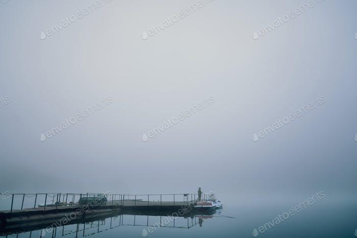 Fischer auf hölzernem Liegeplatz in nebligen Morgen am See