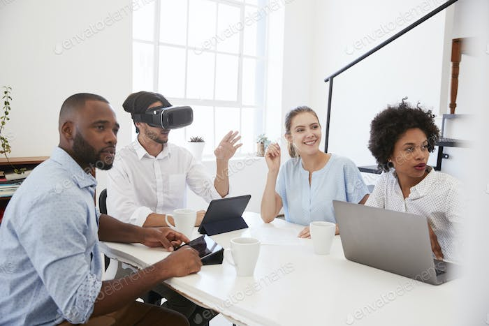 Man in VR goggles at a desk with colleagues in an office