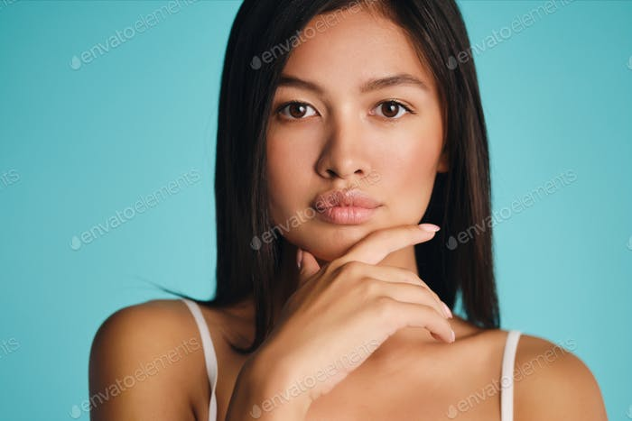 Beautiful confident Asian brunette girl thoughtfully looking in camera over colorful background