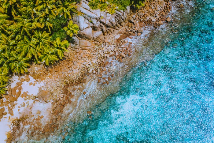 Aerial drone helicopter view of crystal clear turquoise water and amazing granite rocks. La Digue