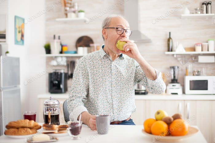 Elderly man bitting green apple