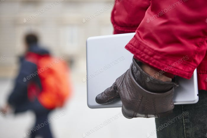 Woman holding a tablet in a city downtown. Winter time