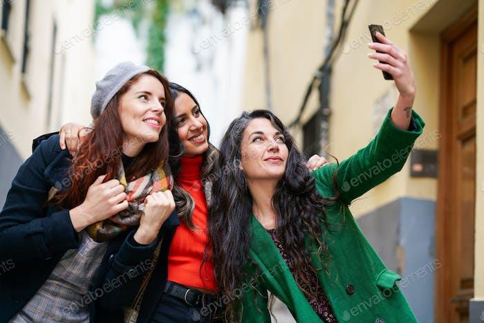 Gruppe von drei glücklichen Frau zu Fuß zusammen im Freien