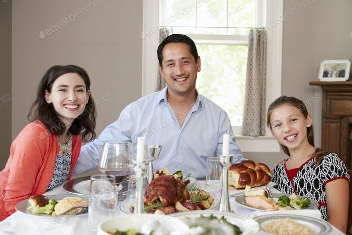 Jewish family at Shabbat dinner table smiling to camera