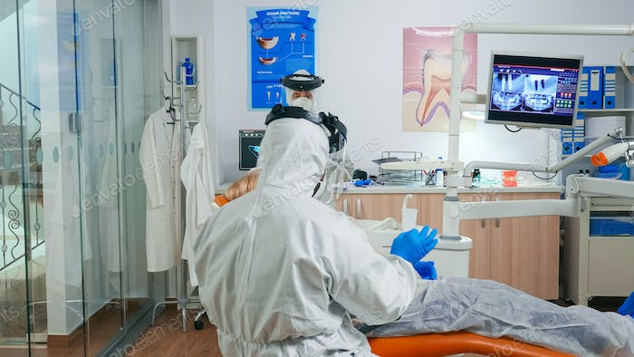 Orthodontist in protection suit explaining dental surgery