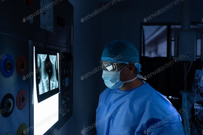 Side view of Caucasian male surgeon reading x ray in operating room at hospital
