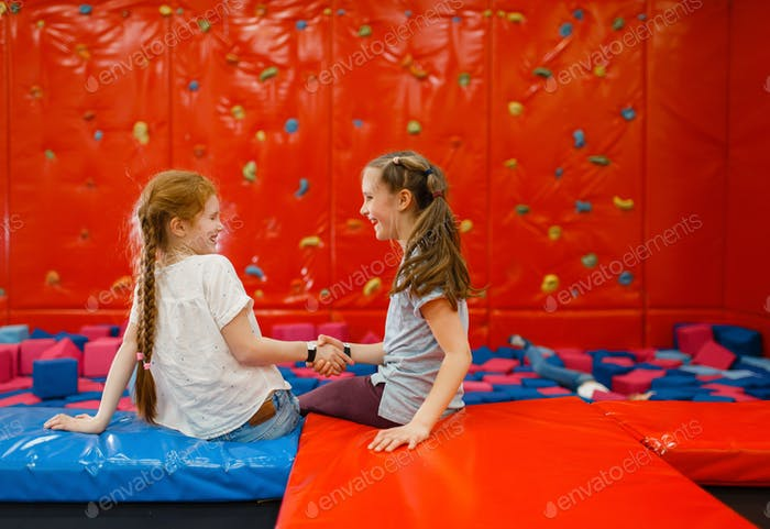 Girlfriends plays among soft cubes, playground