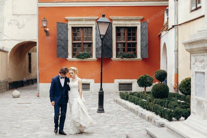 Braut und Bräutigam zu Fuß im Freien in Hochzeitskleidung
