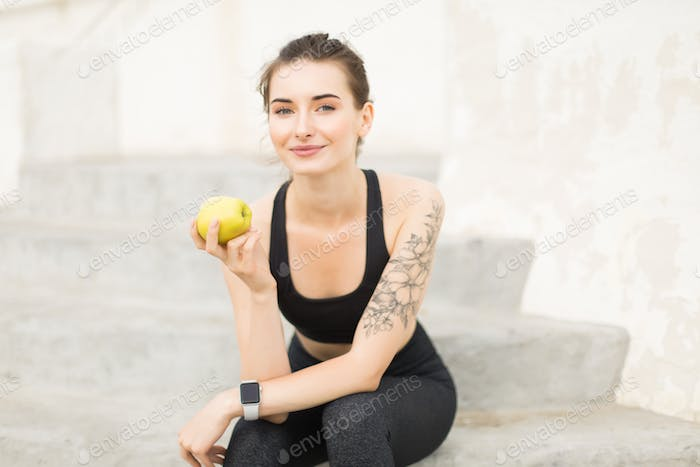 Young beautiful woman in sporty top and leggings holding apple i