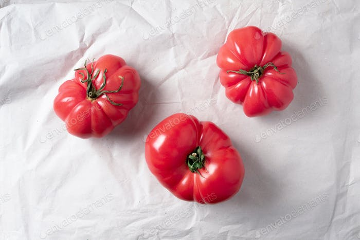 Ugly tomatoes on craft paper background. Concept of zero waste production. Top view. Copy space. Non