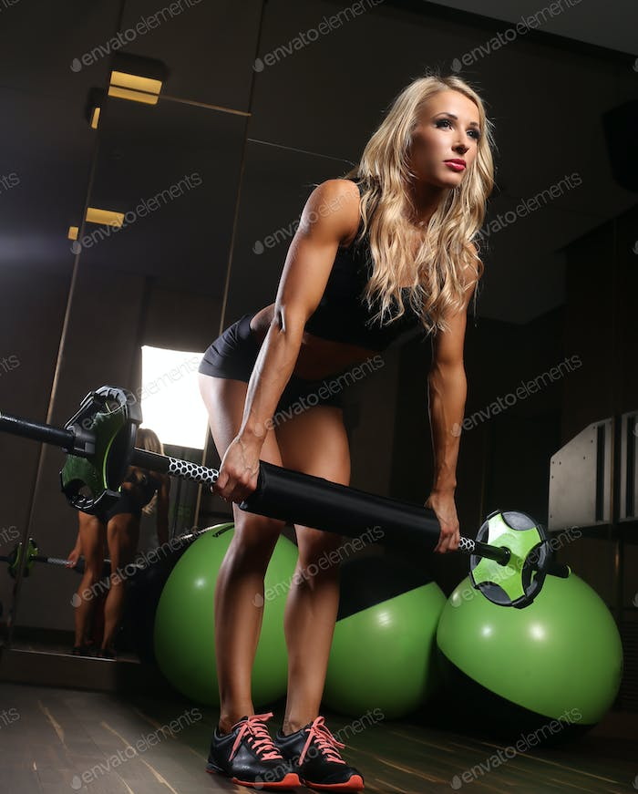 Awesome blond female doing exercises in a gym.