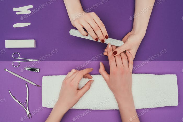 cropped image of manicurist filing nails with nail file