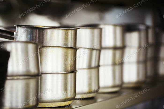Close up of a stack of stainless steel pots in a restaurant kitchen.