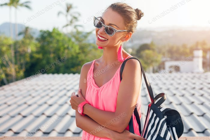 young pretty lady standing on balcony on bright summer day in pink dress