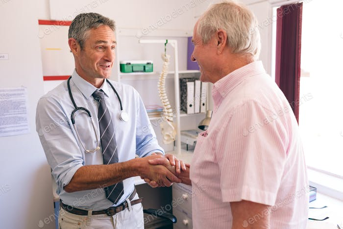 Male doctor interacting with senior male patient in clinic at retirement home