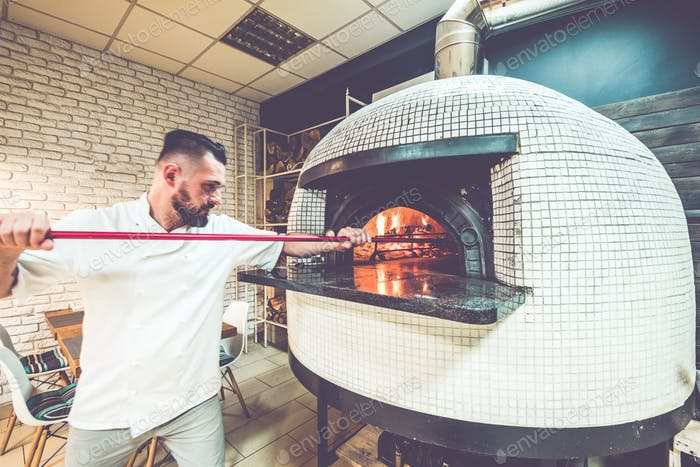Pizza chef in action at local pizzeria business
