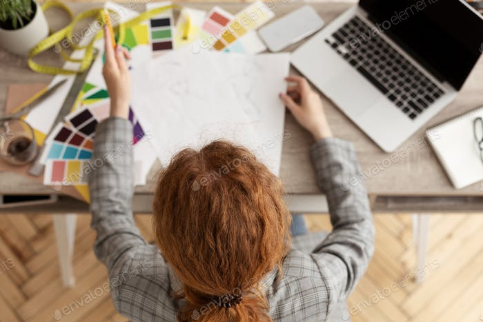 Young female fashion stylist drawing sketches at home