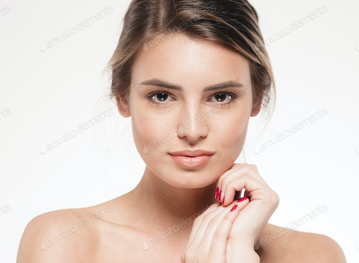 Beautiful woman touching her face looking camera portrait.