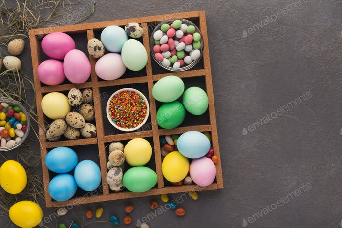 Colored easter eggs and small candies in frame on gray background