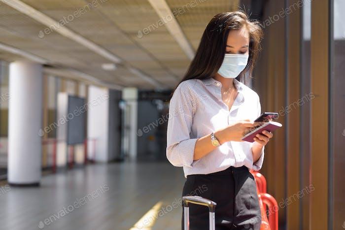 Joven mujer turista asiática con máscara usando el teléfono y la celebración de pasaporte en el aeropuerto