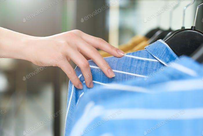 Mano de niña acostada en perchas de tienda con ropa