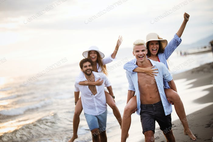 Group of people running on beach and enjoying summer holiday