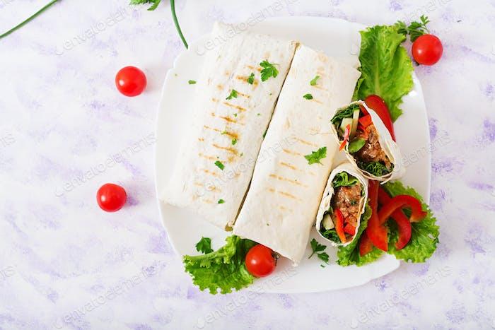 Burritos wickelt mit Hackfleisch und Gemüse auf einem hellen Hintergrund. Flache Lag. Ansicht von oben