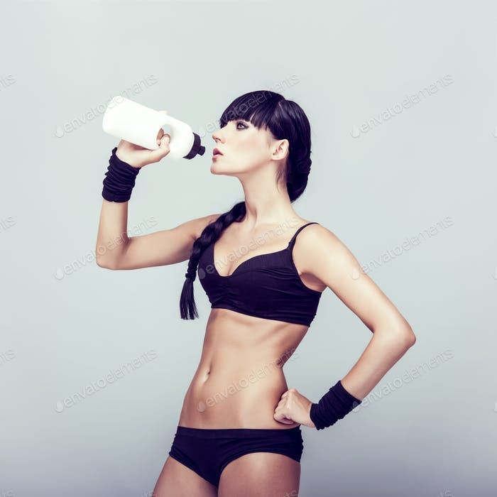 sporty muscular woman drinking water