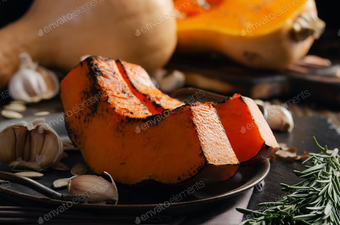 Baked pumpkin slices on metal tray on rustic kitchen wooden table
