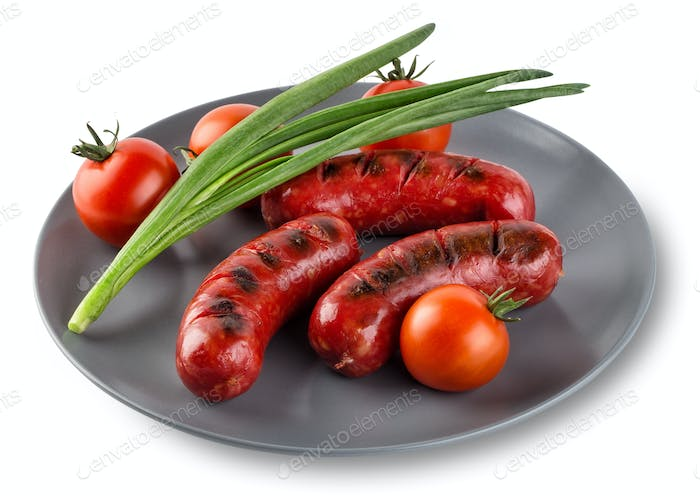 Attractive sausages with tomatoes and onions  on gray plate