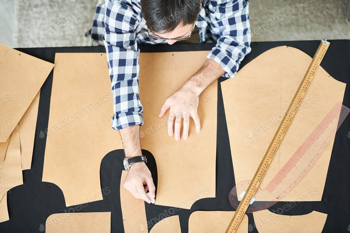 Man applying dress patterns on textile