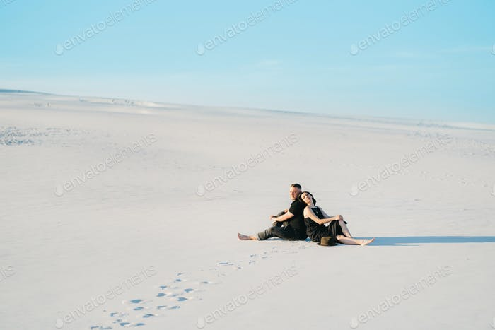 young couple a guy and a girl with joyful emotions in black clothes walk through the white desert