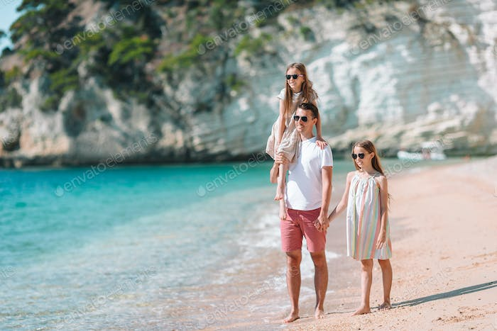 Happy beautiful family of dad and kids on white beach
