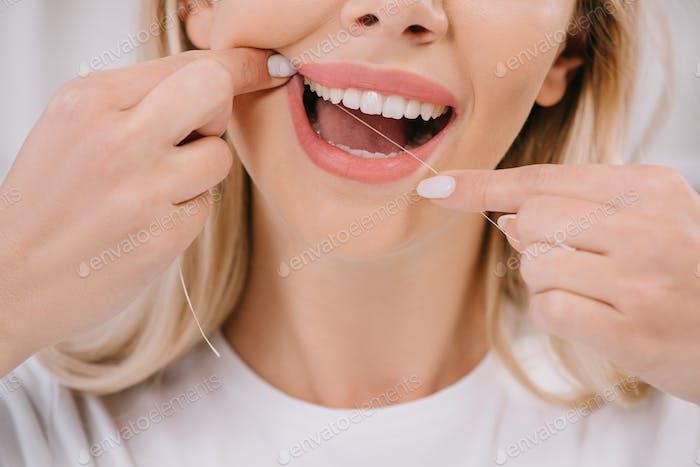 abgeschnittene Ansicht einer Frau, die Zähne mit Zahnseide