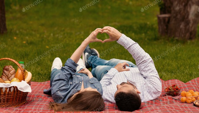 Pair of sweethearts making heart with hands to show their love during picnic at park