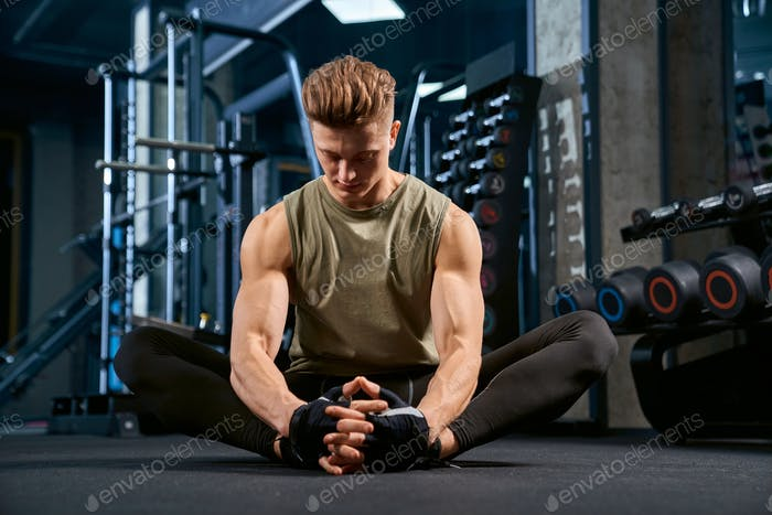 Bodybuilder doing butterfly stretch on floor in gym