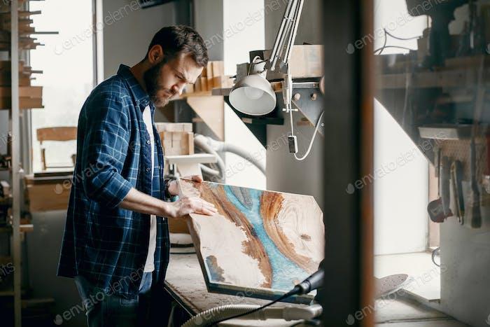El hombre está procesando con madera por máquina de pulido