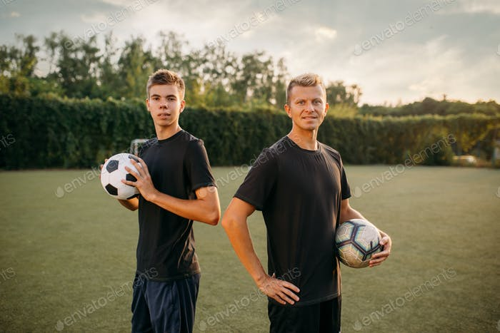 Two male soccer players holding balls in hands