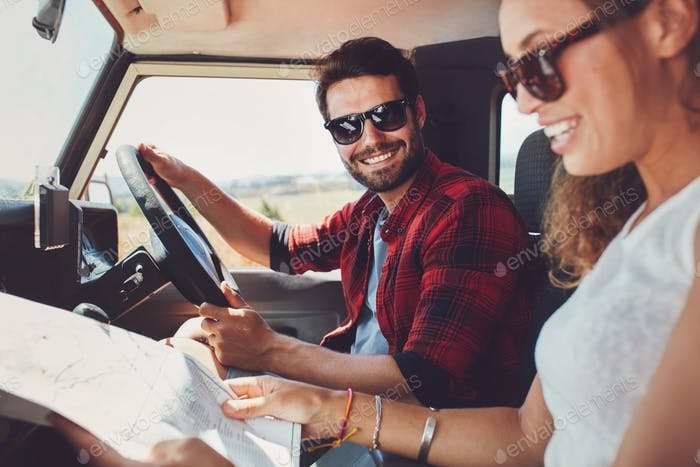 Young couple sitting inside their car with map
