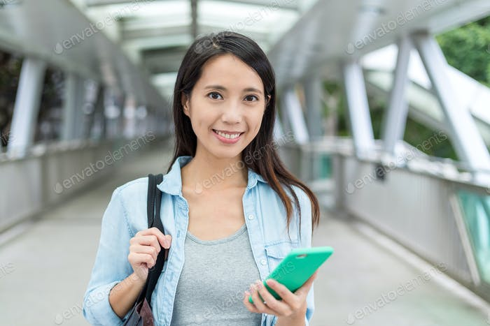 Frau hält Handy auf der Straße von Hong Kong