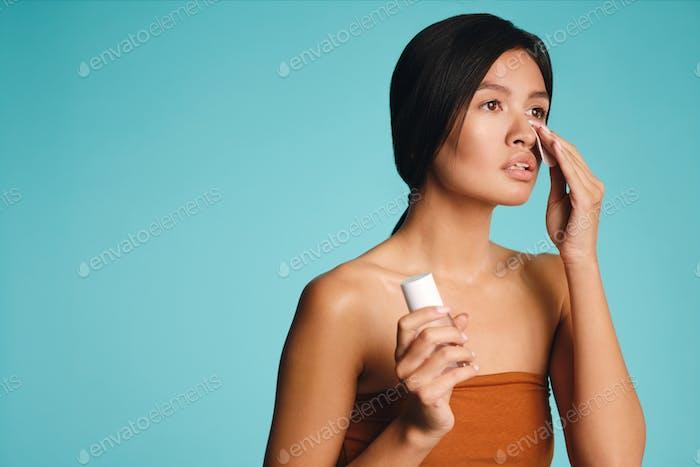 Attractive Asian brunette girl dreamily looking away cleaning face with sponge