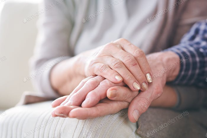 Hands of mature couple